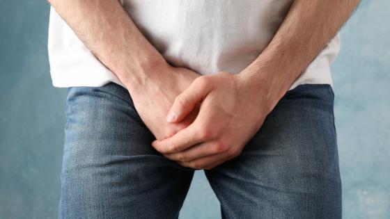 uomo dolorante con mano sulle parti genitali